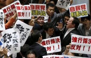 Opposition lawmakers hold signs opposing the vote and security bills as the bills were voted on at the House of Representatives special committee on security bills on Wednesday. Picture courtesy: Yomiuri Shimbun
